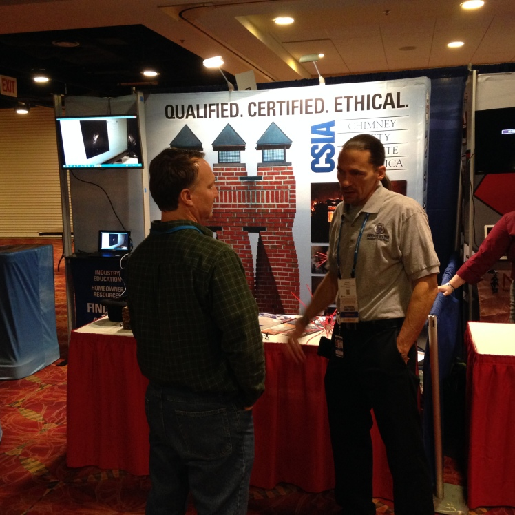 CSIA Certified Chimney Sweep Michael Segerstrom, a member of our board of directors, talks to ASHI attendee John Alastick, on day 1 of the show, Jan. 7, 2015.